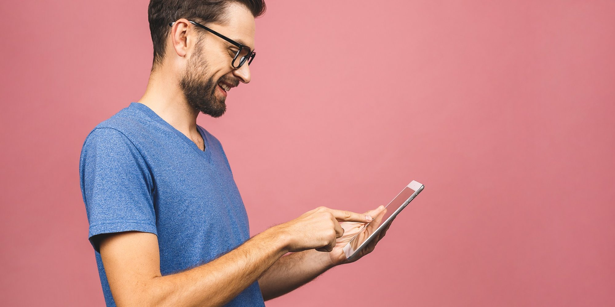 Happy young man in casual standing and using tablet isolated over pink background.